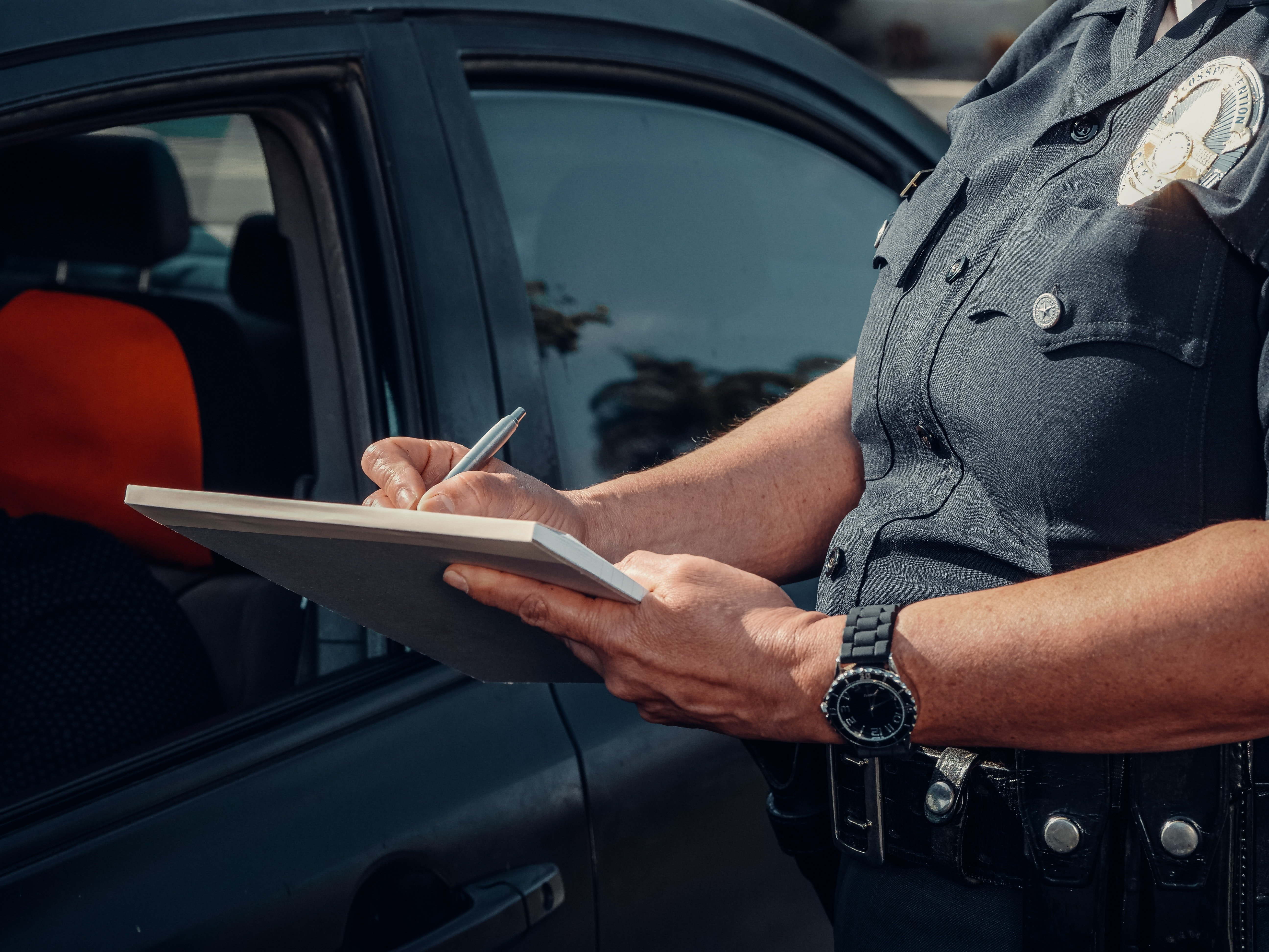 A police officer brings a driver to book and writes them a fine   Photo: Pexels/Kindel Media