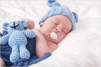Un bébé endormi avec sa sucette. | Shutterstock