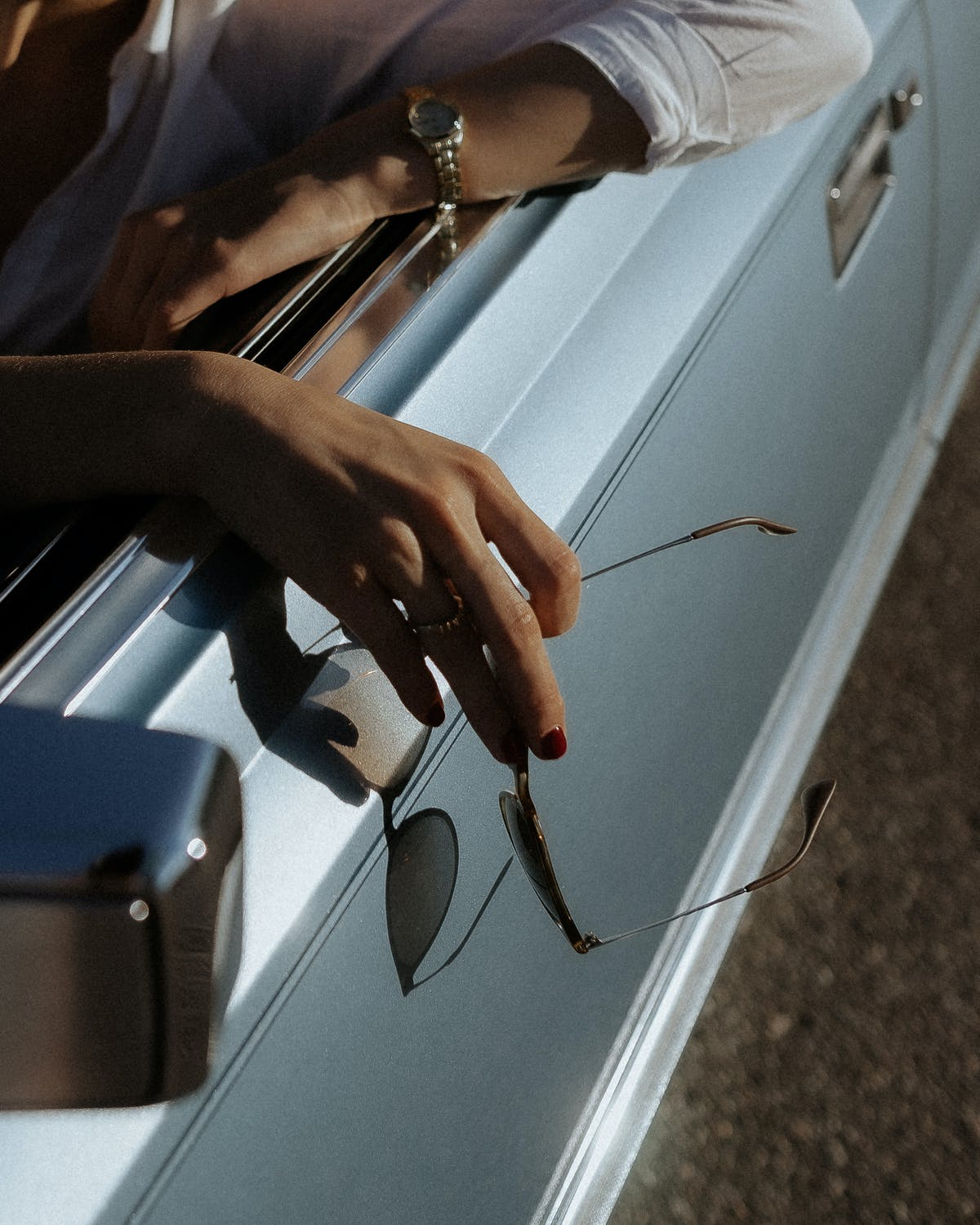 A woman's arms leaning against the window of a fancy car   Source: Pexels