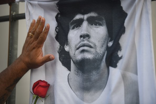 Un fan met sa main avec une rose sur un T-shirt avec la photo de la star du football Diego Maradona le jour de sa mort.  |Photo : Getty Images