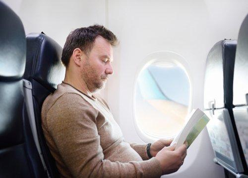 Un homme qui lit pendant son vol dans un avion | Photo : Shutterstock