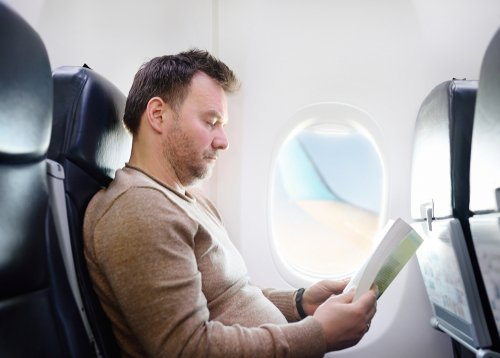 A man reading during his flight on an airplane. | Source: Shutterstock.