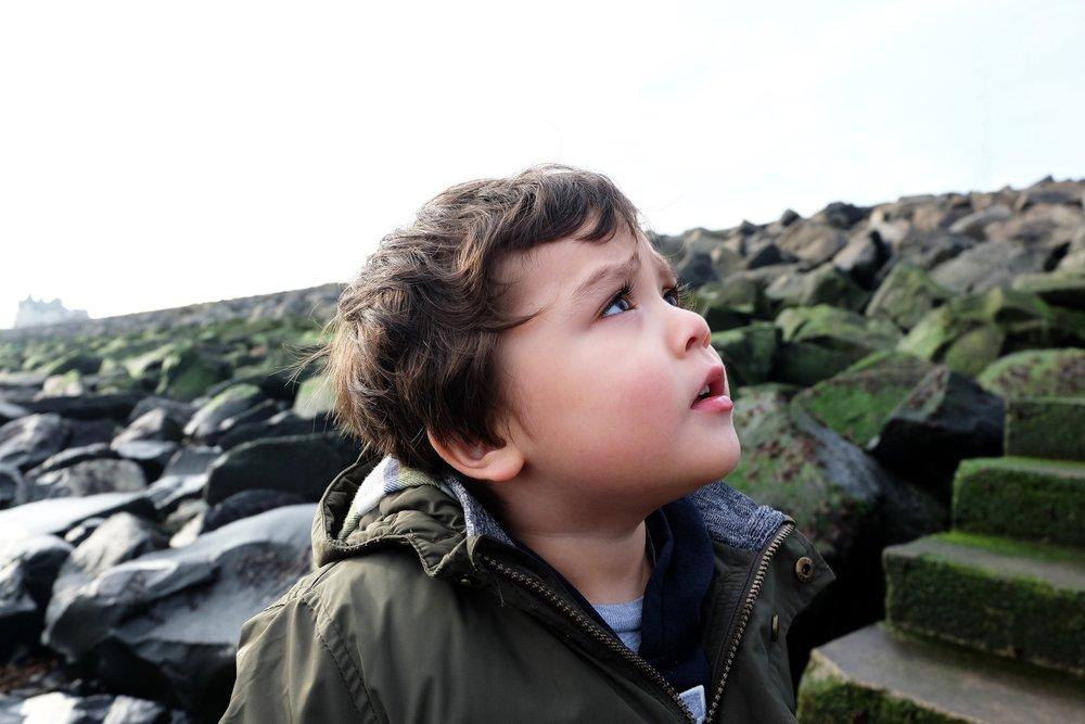 Un petit garçon fronçant les sourcils en regardant vers le ciel | Photo: Shutterstock