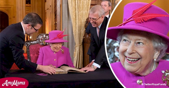 Queen beams in magenta coat to sign a special 'Golden Book' on her last outing before Christmas