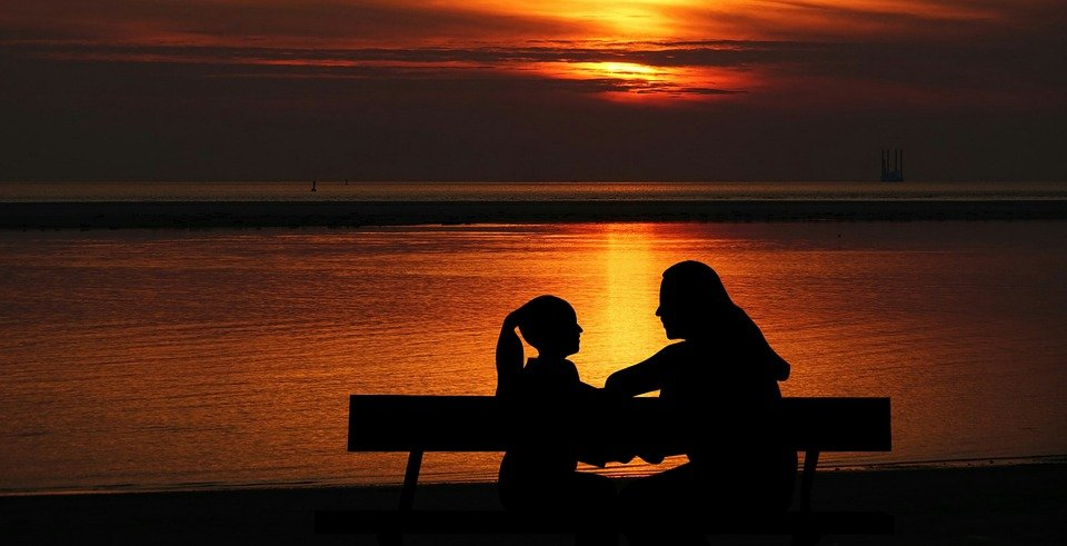 A mother and daughter discussing against the background of the sun setting. | Photo: Pixabay