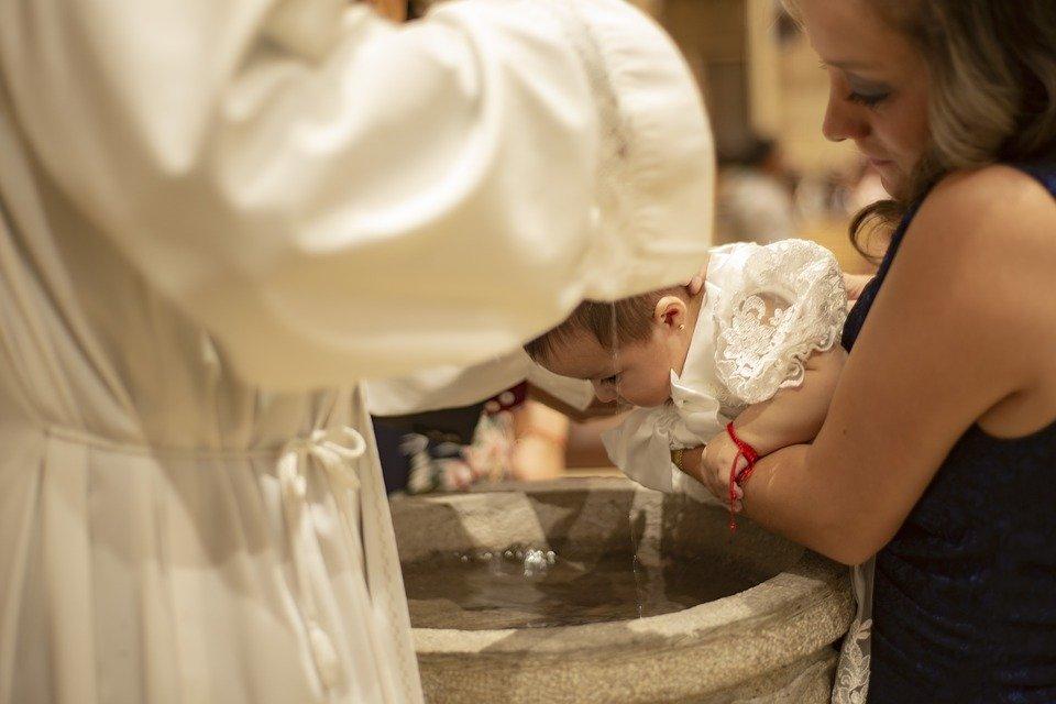 Cura bautizando a un bebé.| Imagen: Pixabay