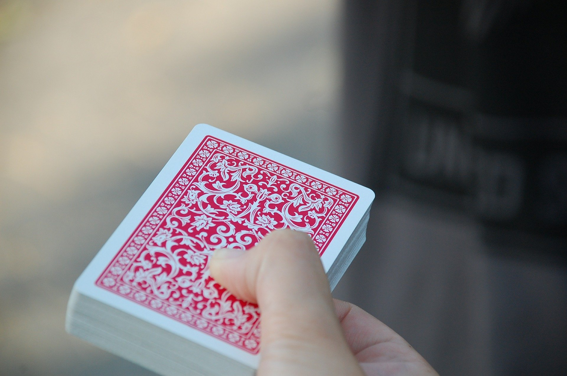 Man holding out a deck of cards.   Source: Pixabay
