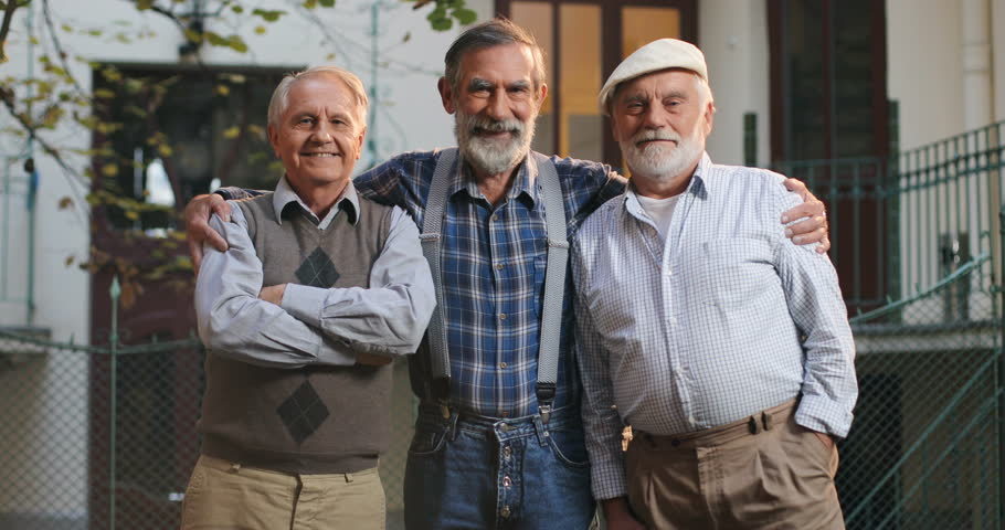 Three old men hugging each other | Photo: Shutterstock