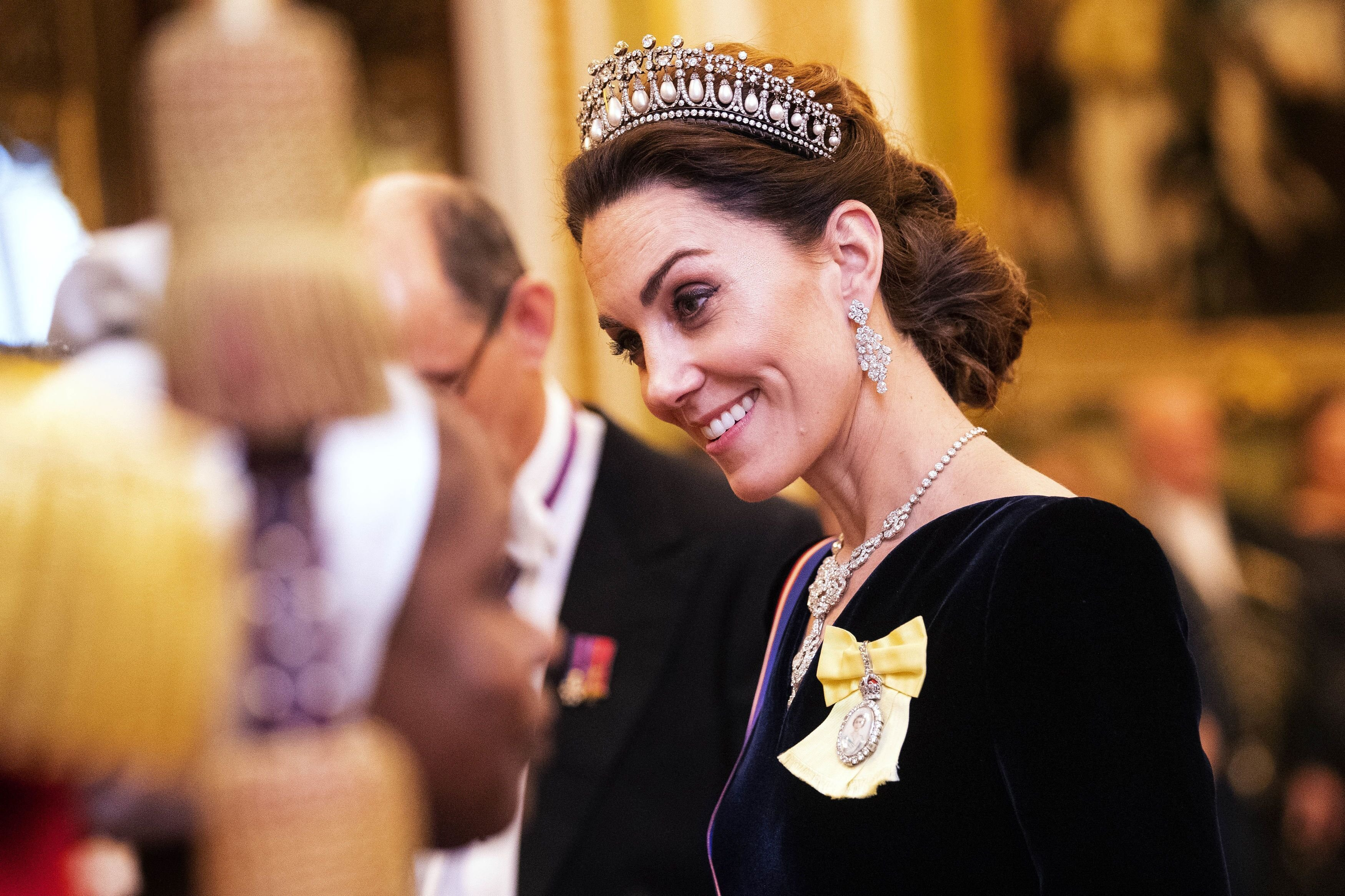 Kate Middleton talks to guests at an evening reception for members of the Diplomatic Corps at Buckingham Palace. | Source: Getty Images