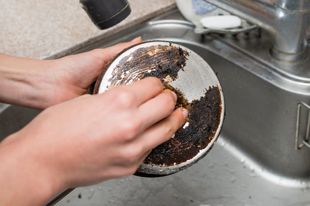 Hand cleaning underneath a dirty pot | Photo: Shutterstock