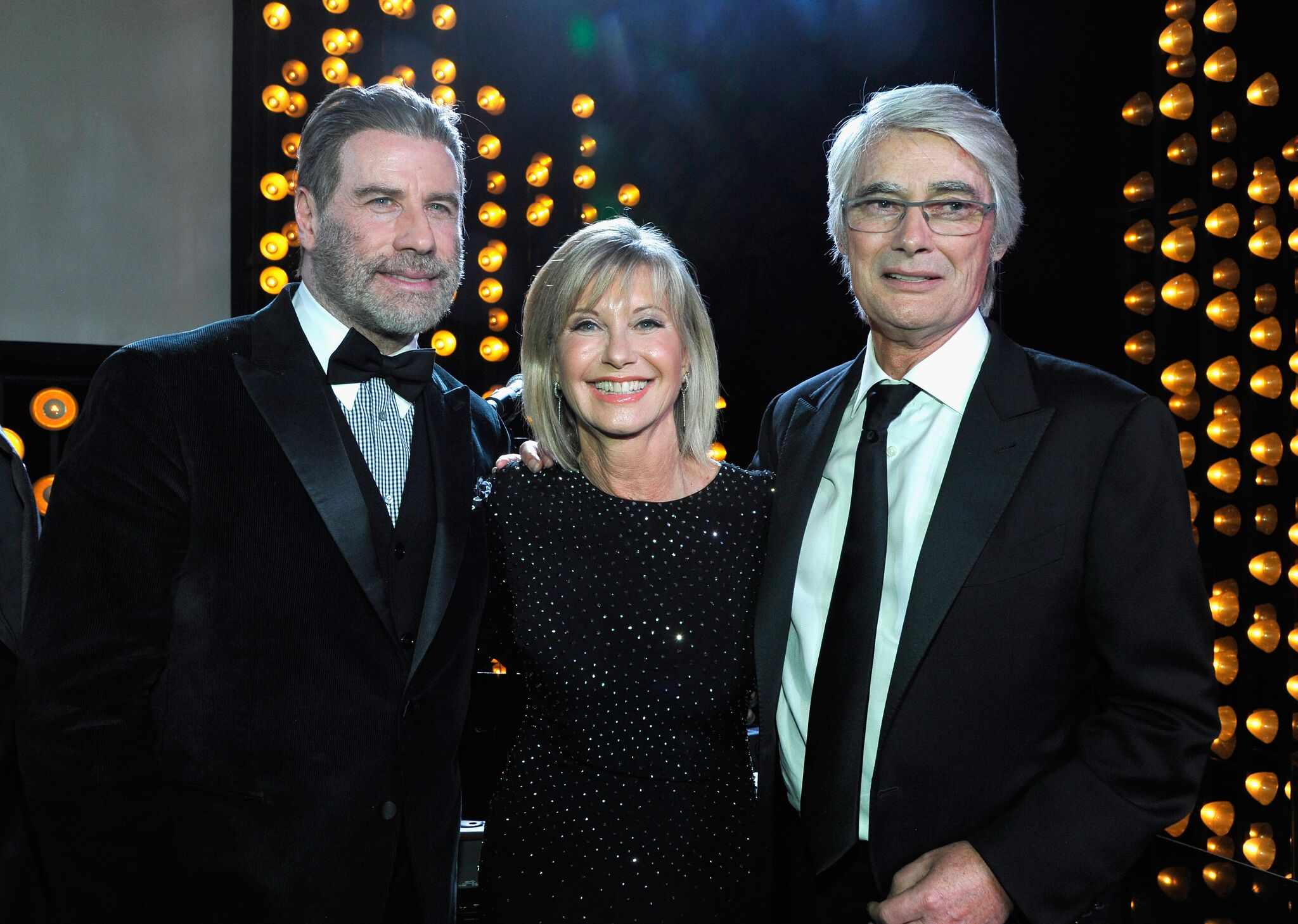 John Travolta, Olivia Newton John and Honoree John Farrar speak onstage during the 2018 G'Day USA Black Tie Gala | Getty Images