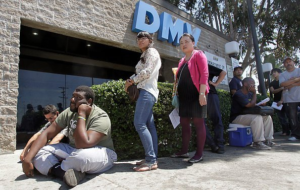 A man sits on the floor as he joined people in a line outside the DMV office, on Tuesday, Aug. 14, 2012, Los Angeles Source: Luis Sinco/Los Angeles Times via Getty Images