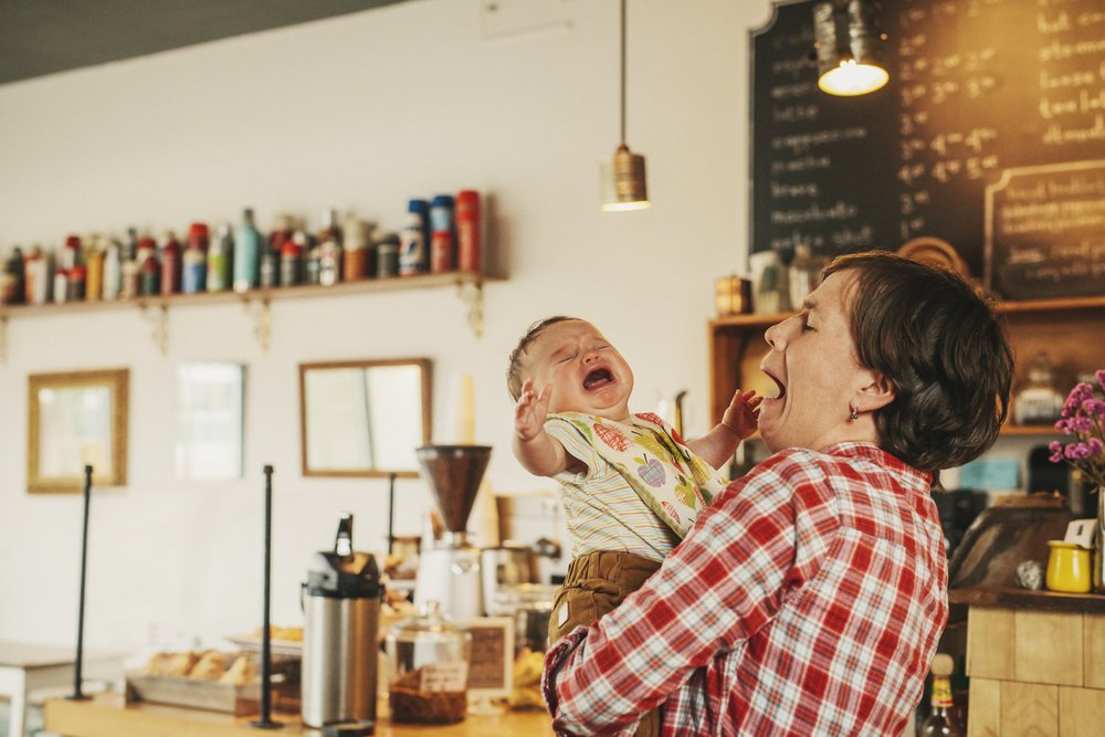 A woman holding a crying baby in a coffee shop. | Photo: Shutterstock.