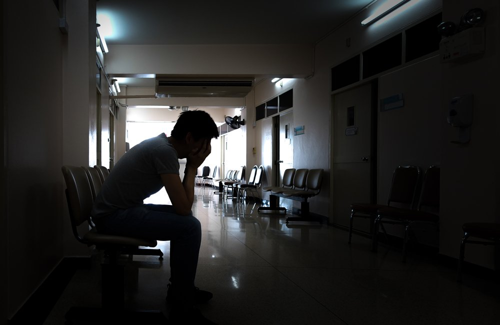 A silhouette of a crying man waiting in the hospital after an emergency | Photo: Shutterstock/iphotosmile