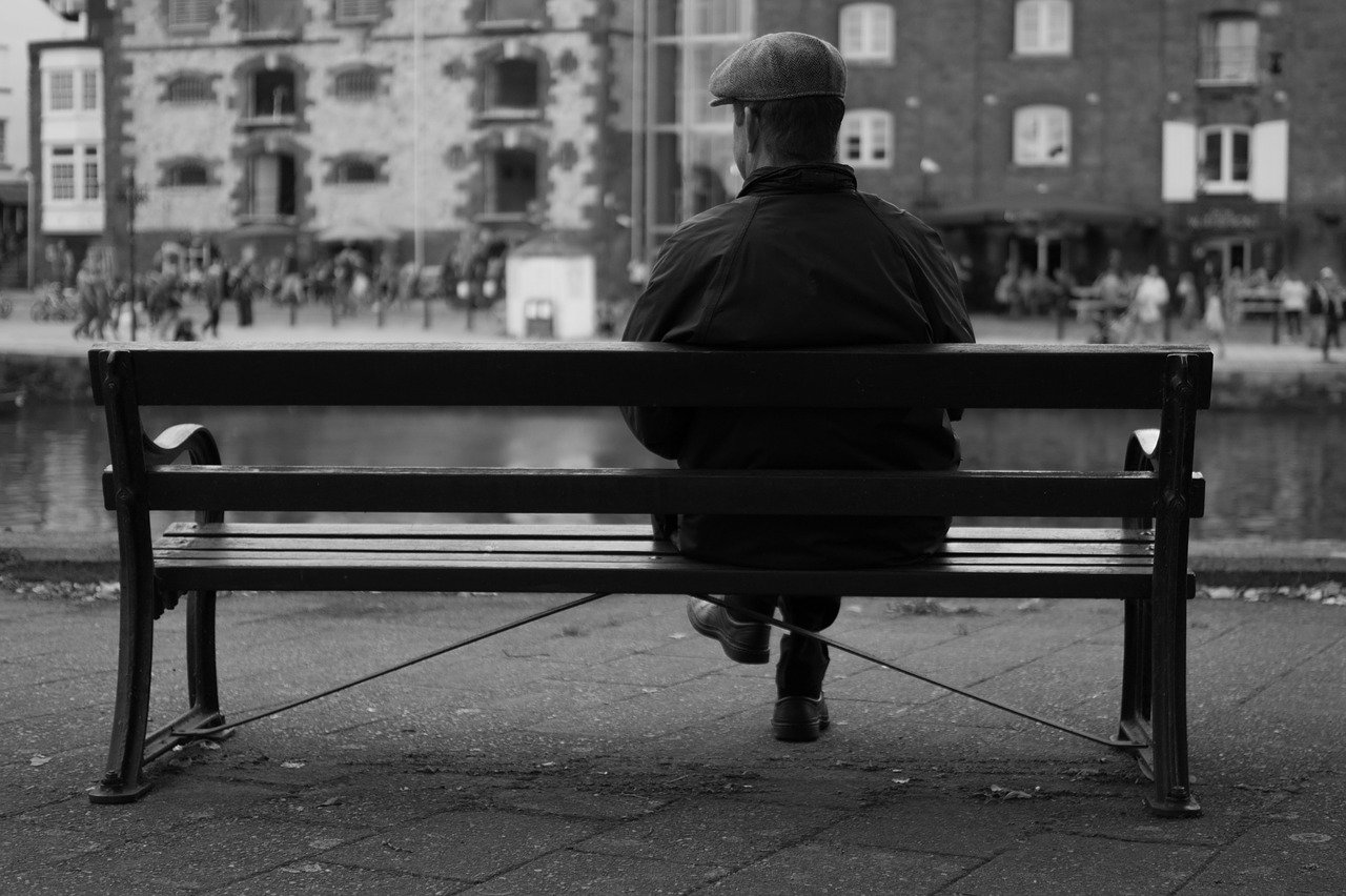 A black-and-white image of a man sitting on a bench looking at the view in front of him   Photo: Pixabay