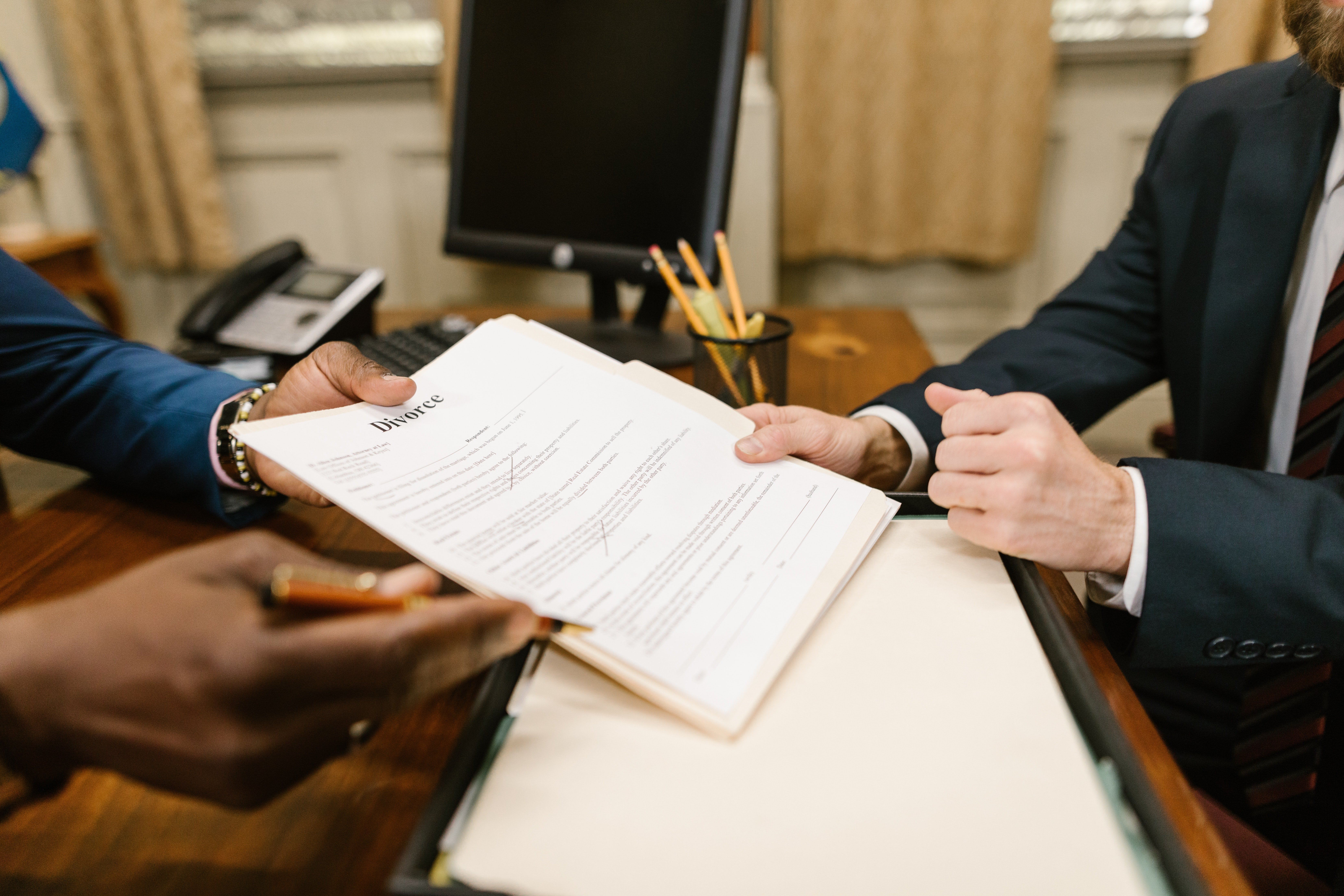 Two people holding divorce papers | Photo: Pexels
