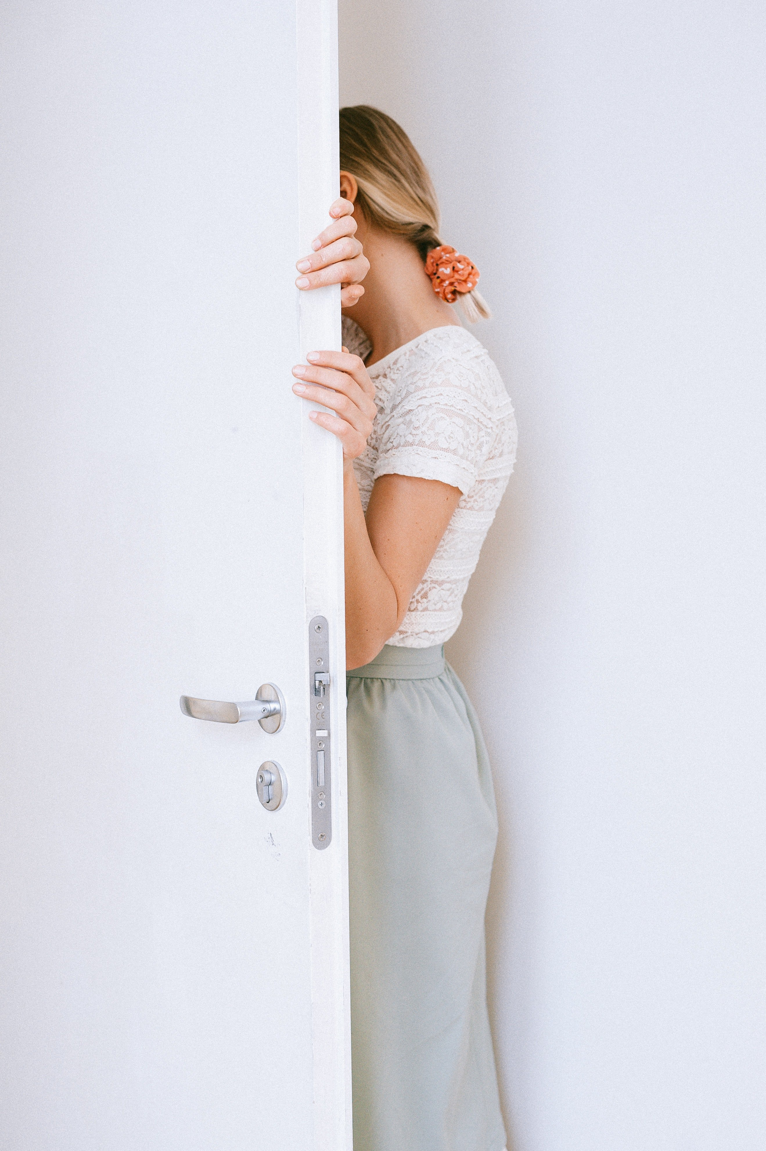 A woman leaning into an open door. | Photo: Pexels