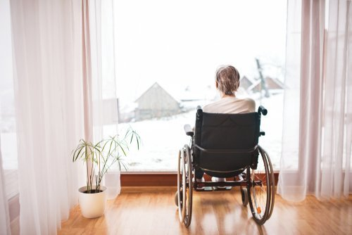 A woman in a wheelchair looking out a window.   Source: Shutterstock.