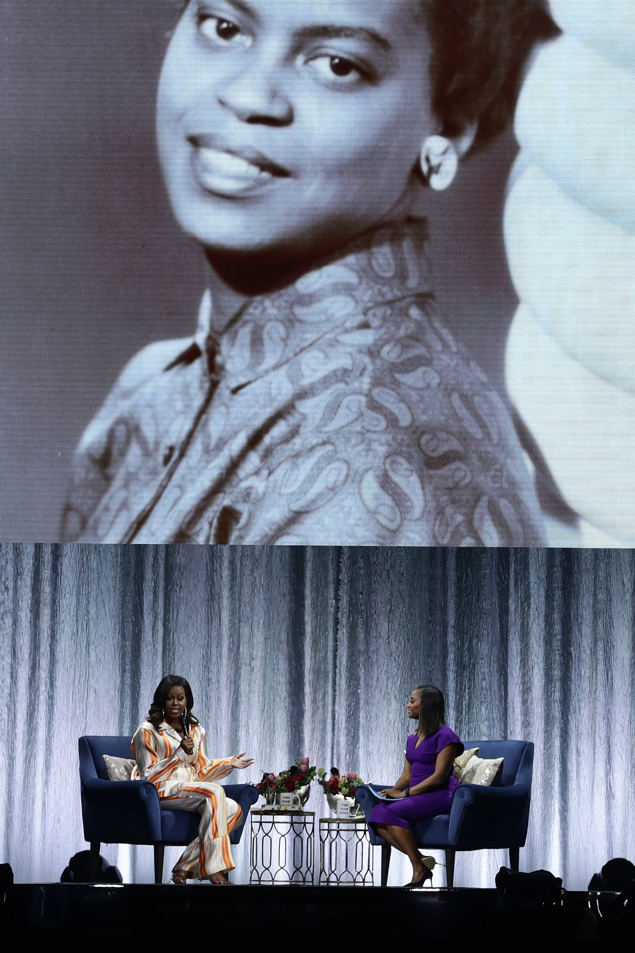 Michelle Obama speaking in front a picture of her younger self | Photo: Getty Images
