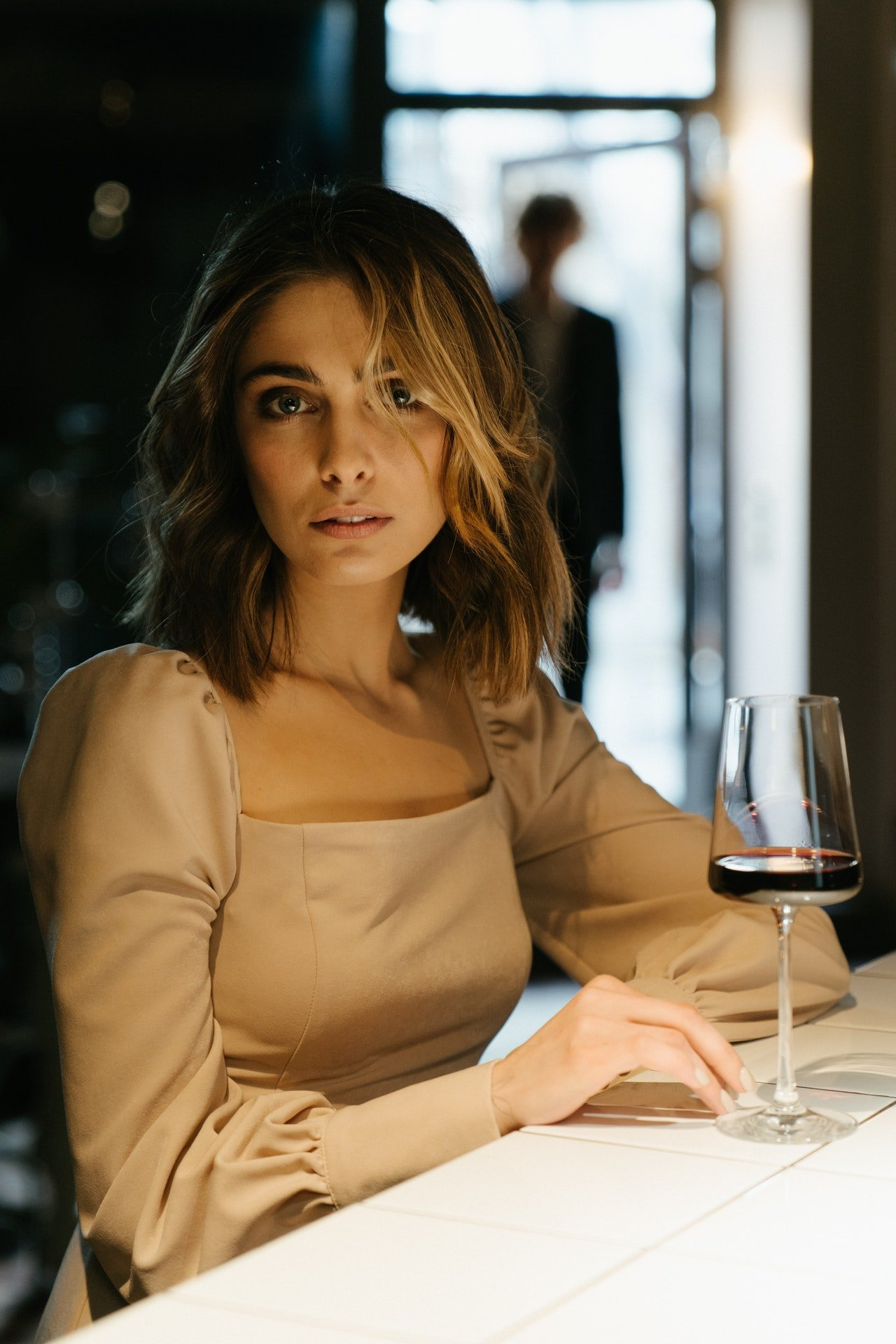 Photo of a woman in a restaurant holding a wine glass | Photo: Pexels