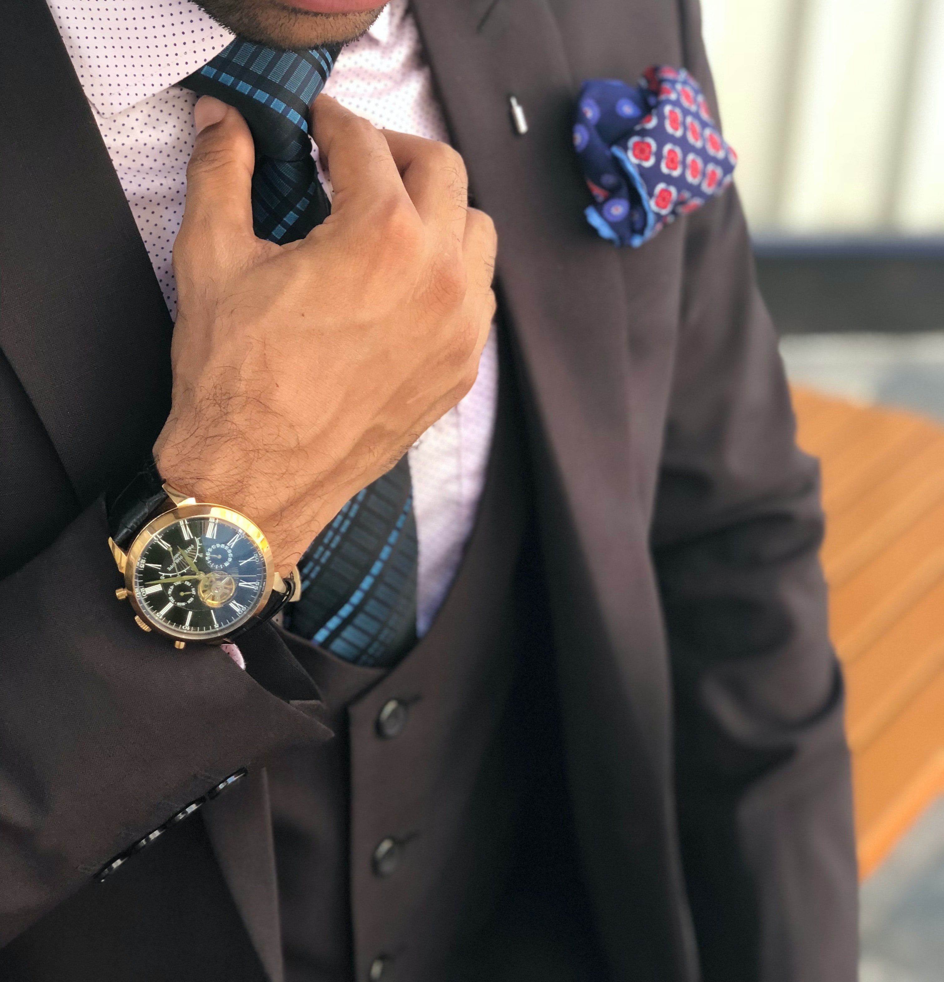 Pictured - A man in a formal suit holding his necktie   Source: Pexels