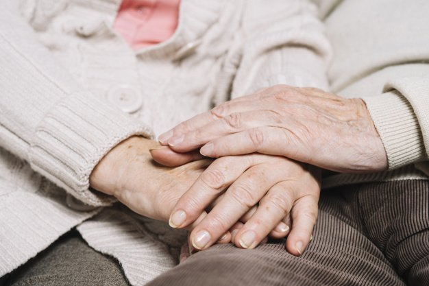 Elderly couple holding hands while sitting together at home. | Photo: Freepik
