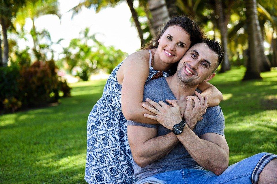 Mujer abrazando a su pareja mientras están sentados sobre el pasto en un parque. | Imagen: Pixabay