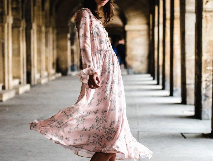 Mujer joven vistiendo un traje rosa caminando por los pasillos de una iglesia. | Imagen: Pixnio