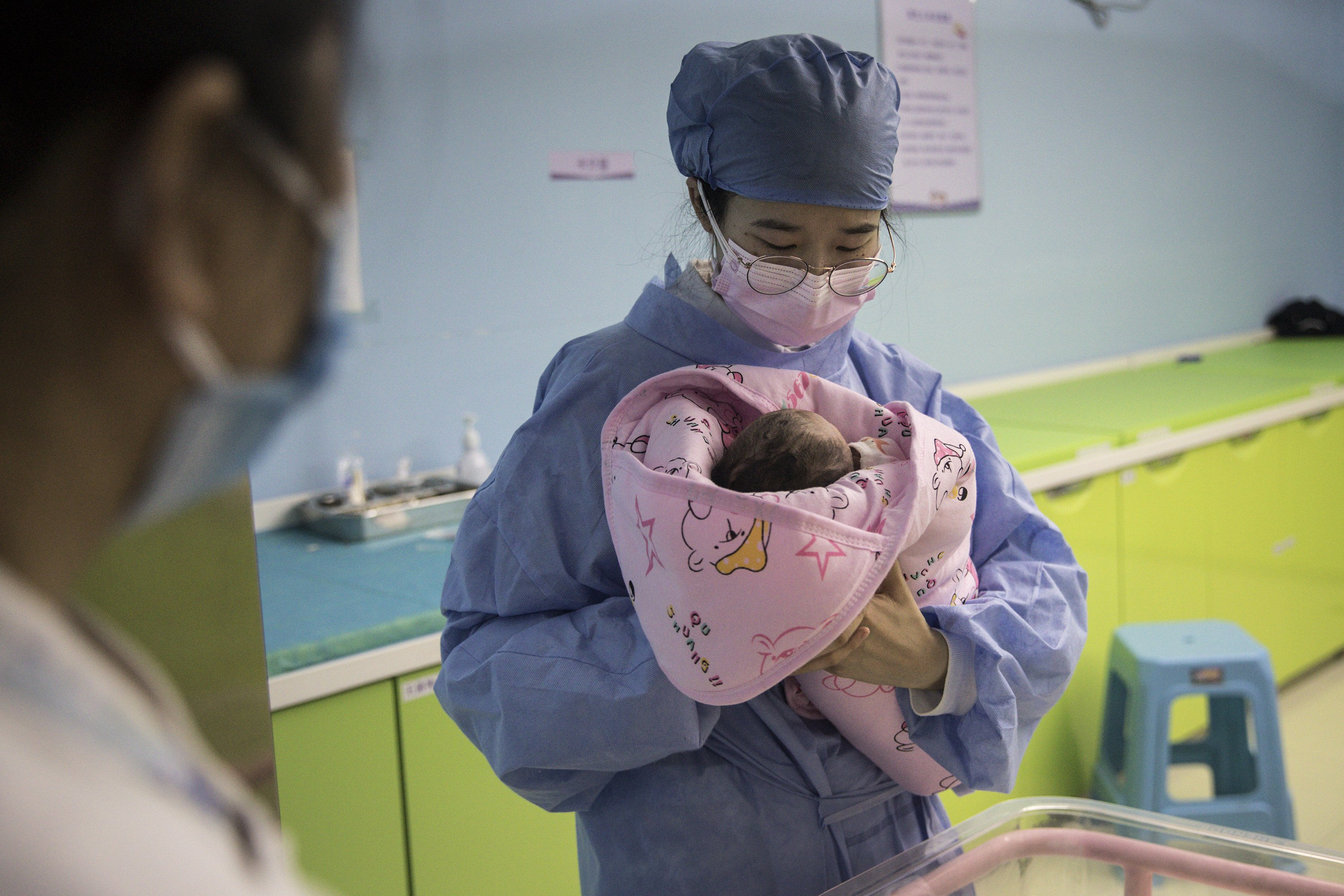 A nurse holds a newborn baby in a private obstetric hospital on February 21, 2020 | Photo: Getty Images