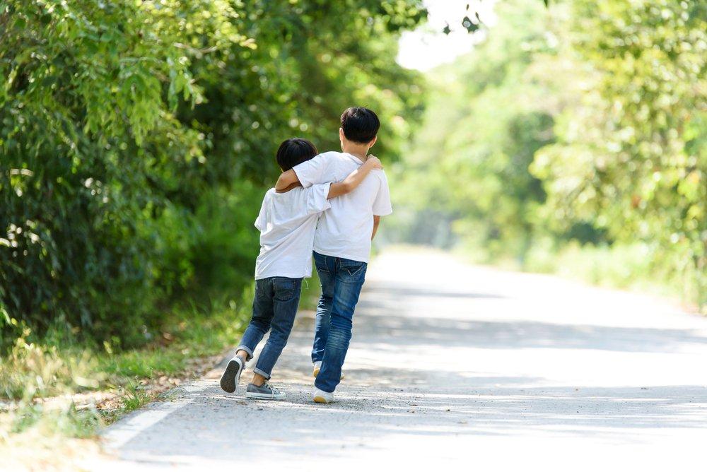 Deux amis marchant ensemble. l Source: Shutterstock