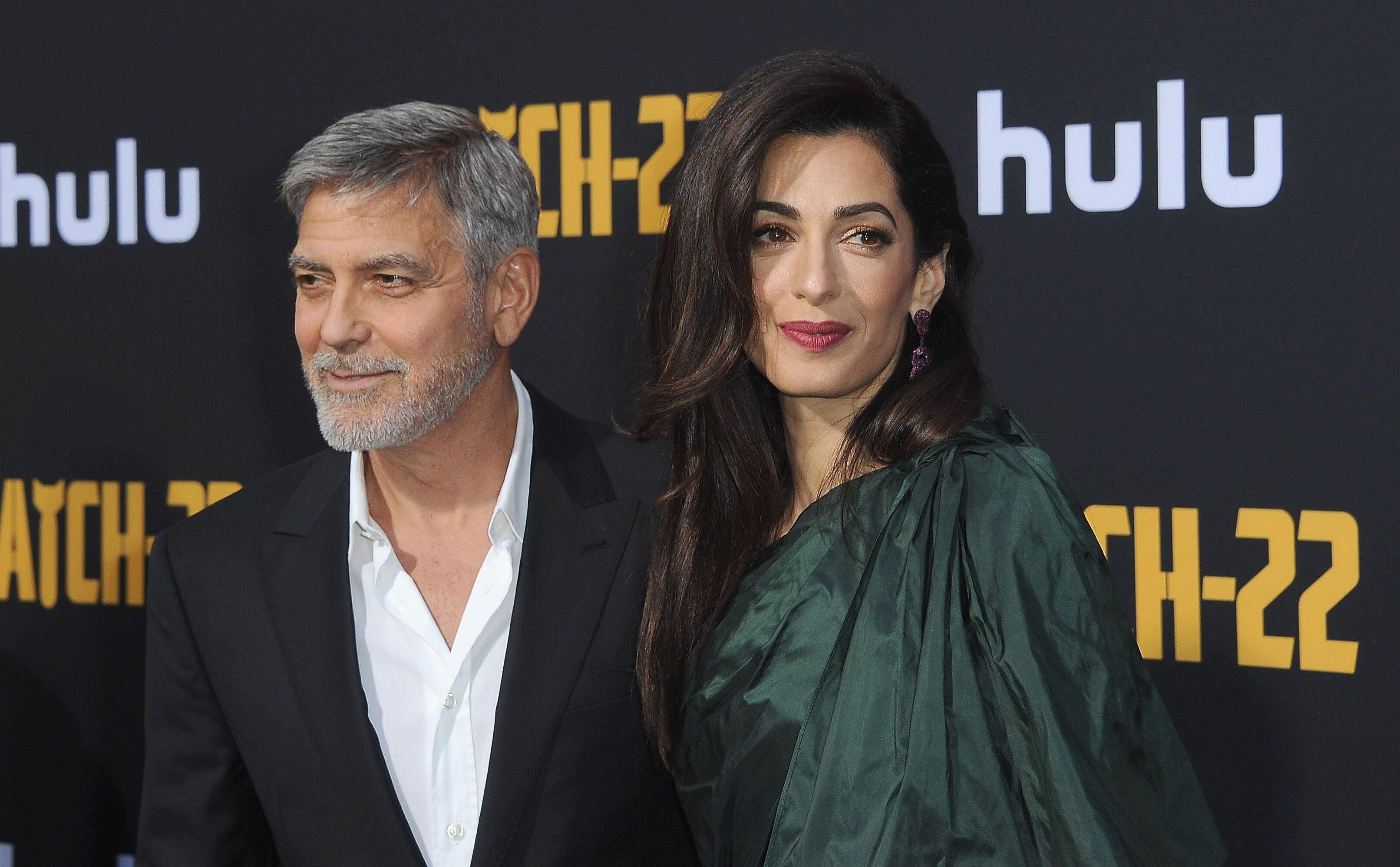 "George and Amal Clooney at the Hollywood premiere of ""Catch-22"" in May 2019. 