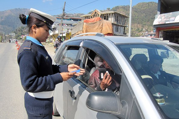 Traffic policewoman checks a driver's documents in Nepal | Photo: Getty Images