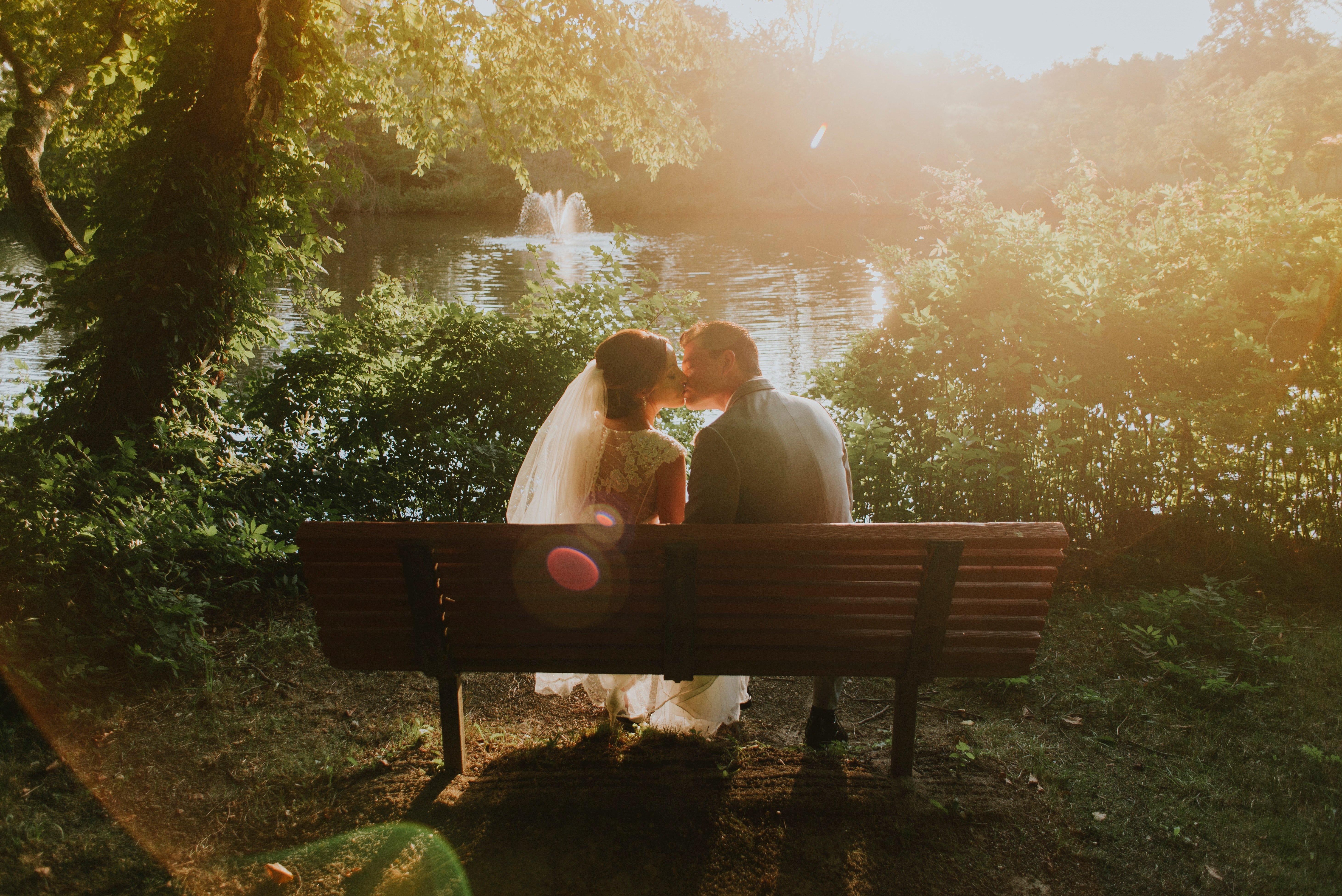 Un couple marié qui s'embrasse sur un banc. l Source: Unsplash