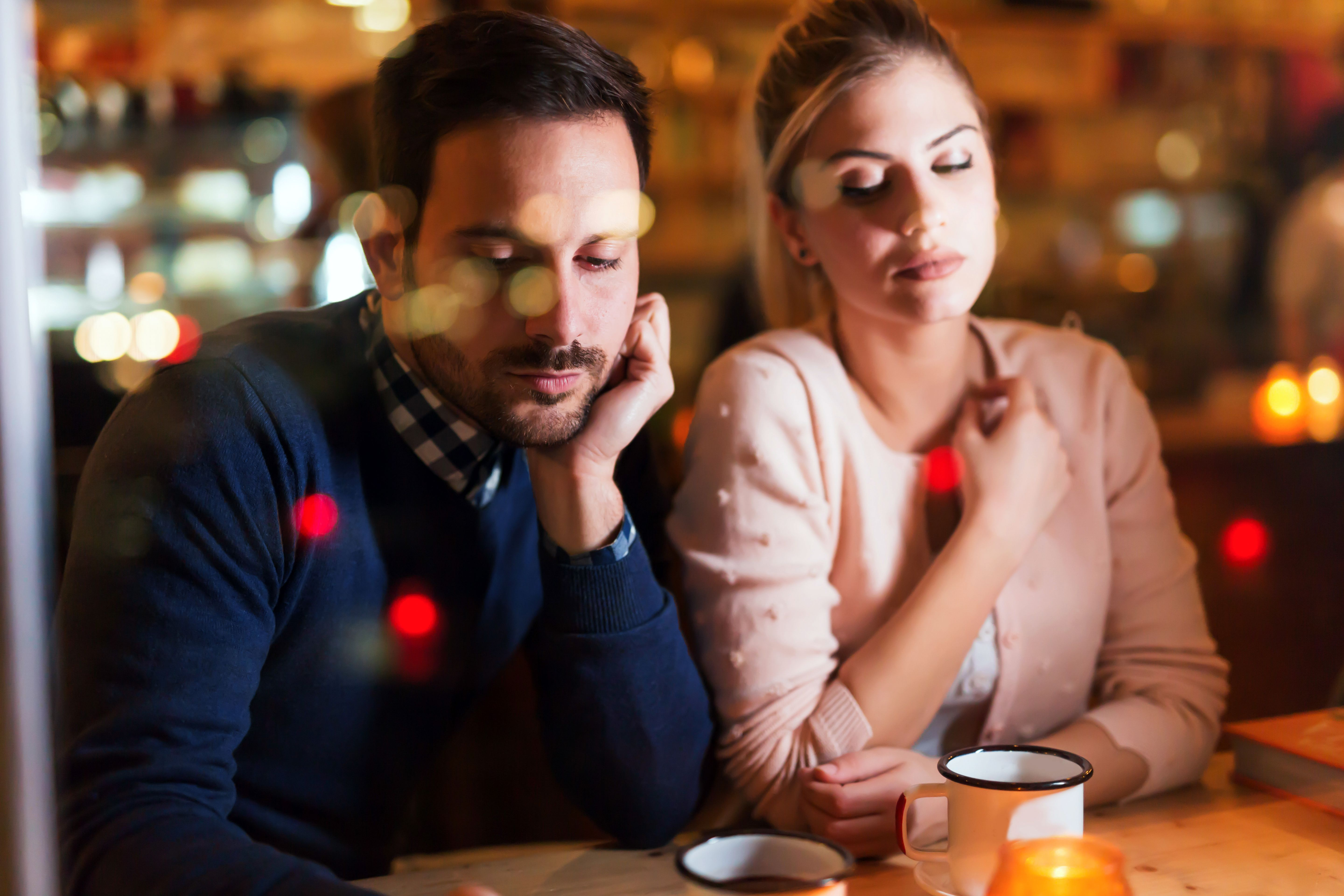 A bored couple in a cafe, showing signs of jealousy. | Photo: Shutterstock