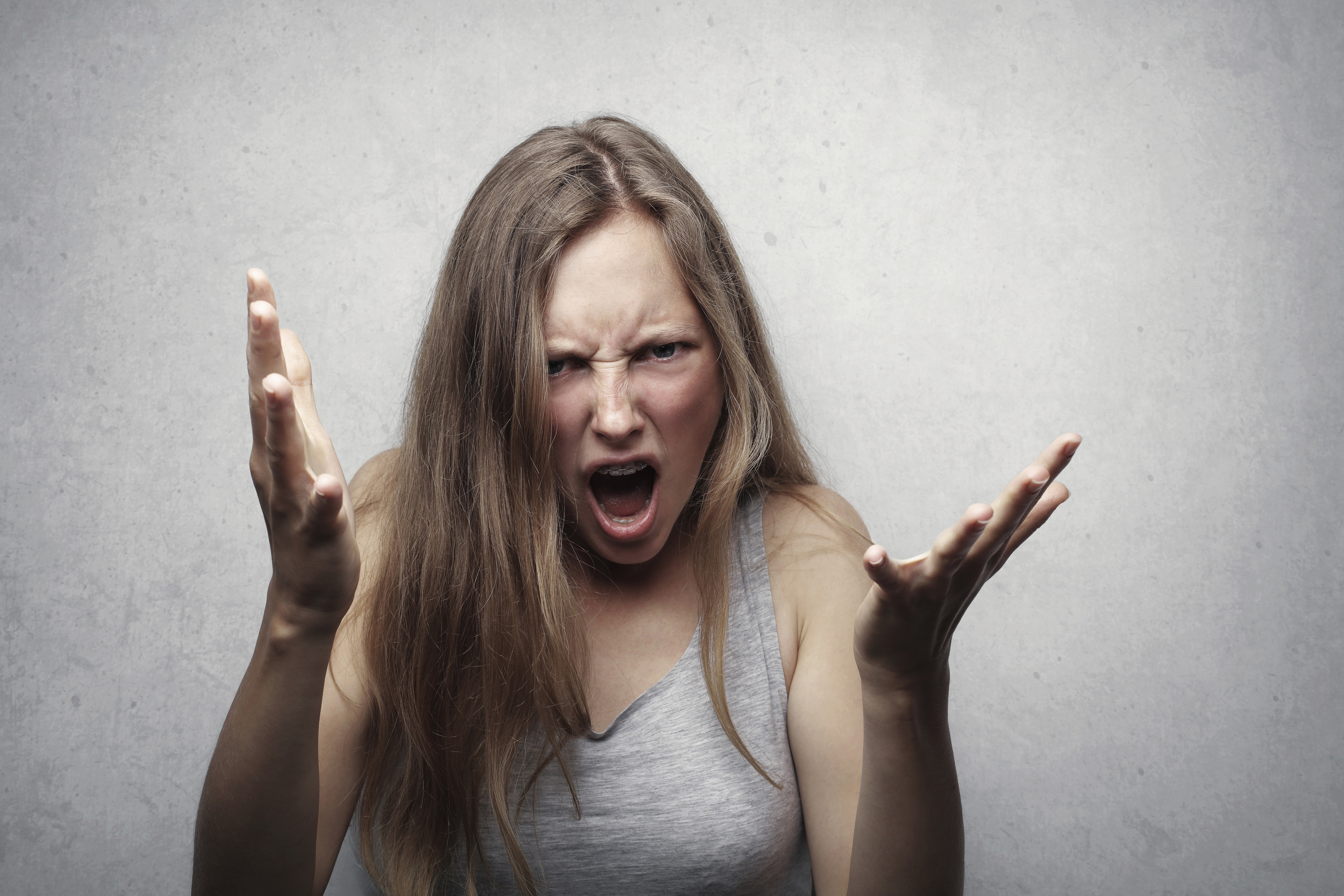 Angry woman in a grey tank top   Photo: Pexels