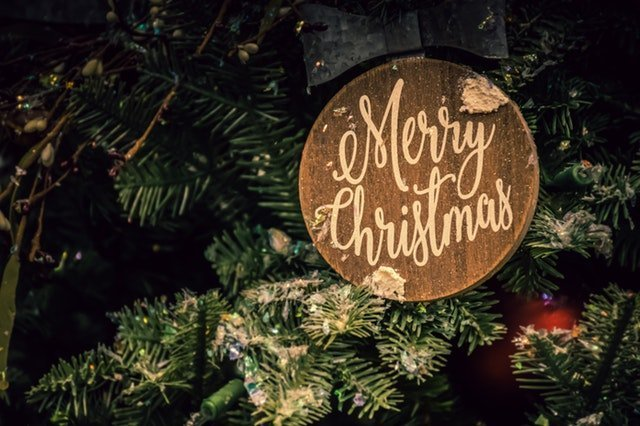 Merry Christmas sign on a Christmas tree | Source: Pexels