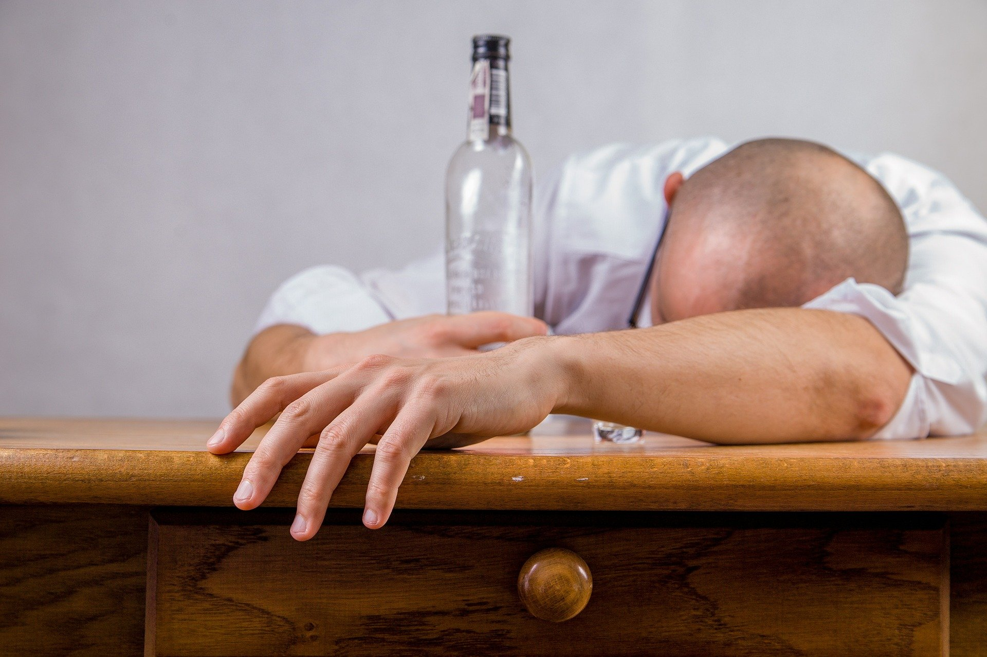 A drunk man lying on a table sleeping while holding on to an alcohol bottle | Photo: Pixabay/Michal Jarmoluk