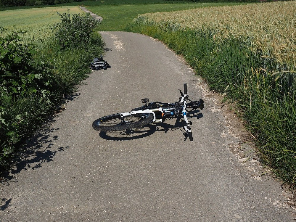 A fallen, damaged bicycle on a paved road. | Image: Pixabay.