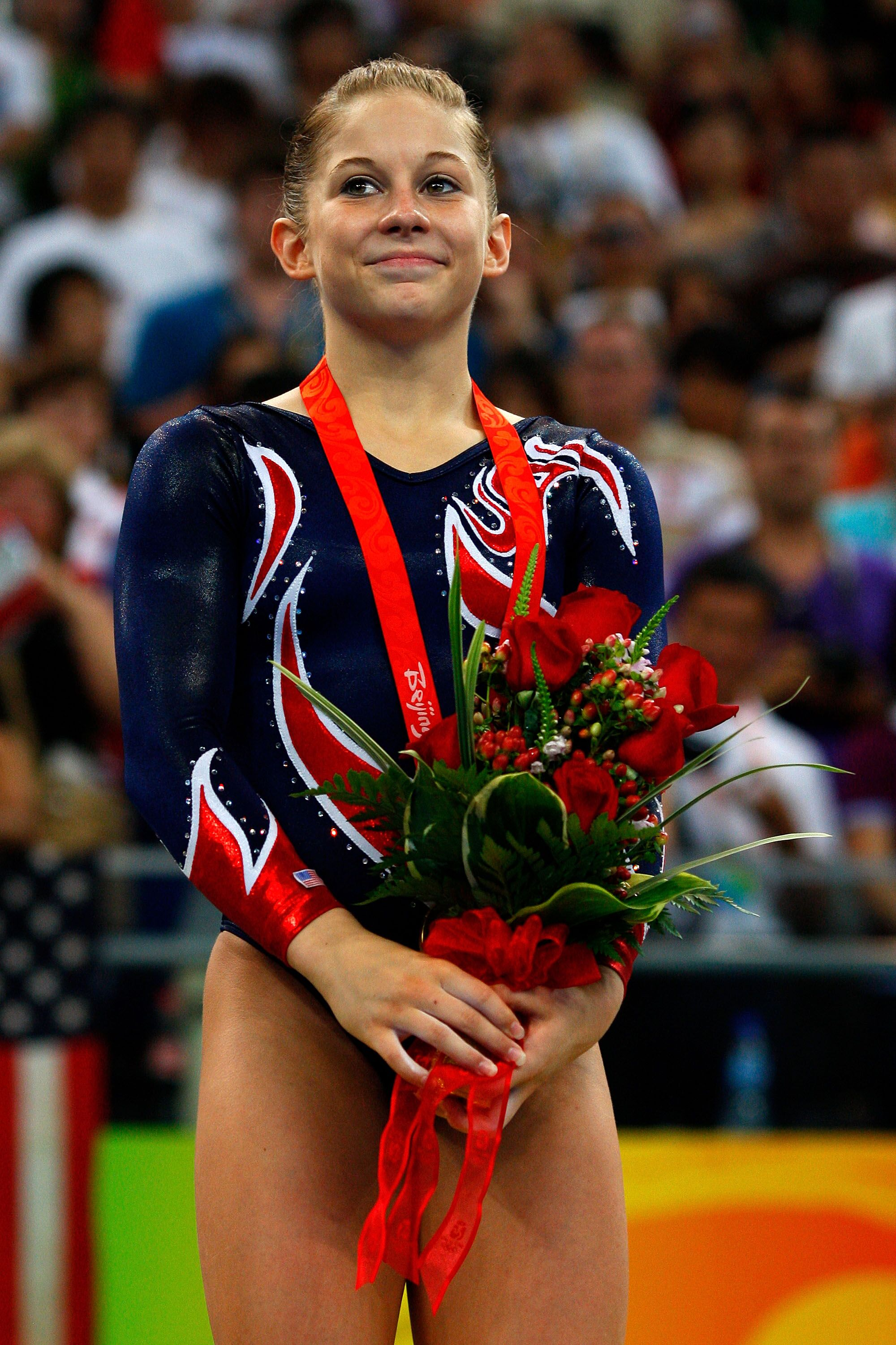 Shawn Johnson of the USA smiles as she stands on the podium during the medal ceremony for the Women's Beam Final at the National Indoor Stadium on Day 11 of the Beijing 2008 Olympic Games on August 19, 2008 in Beijing, China | Photo: Getty Images