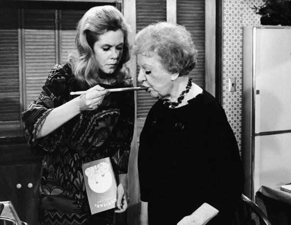 """Elizabeth Montgomery, as Samantha Stephens feeds actress Marion Lorne, as Aunt Clara with a wooden cooking spoon from the episode 'A Majority of Two' of the television sitcom """"Bewitched,"""" April 11, 1968. 