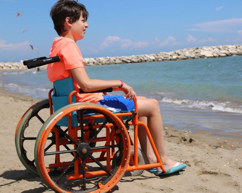 Joven en silla de ruedas con ruedas grandes para moverse sin problemas en la arena de la playa junto al mar en verano. Fuente: Shutterstock