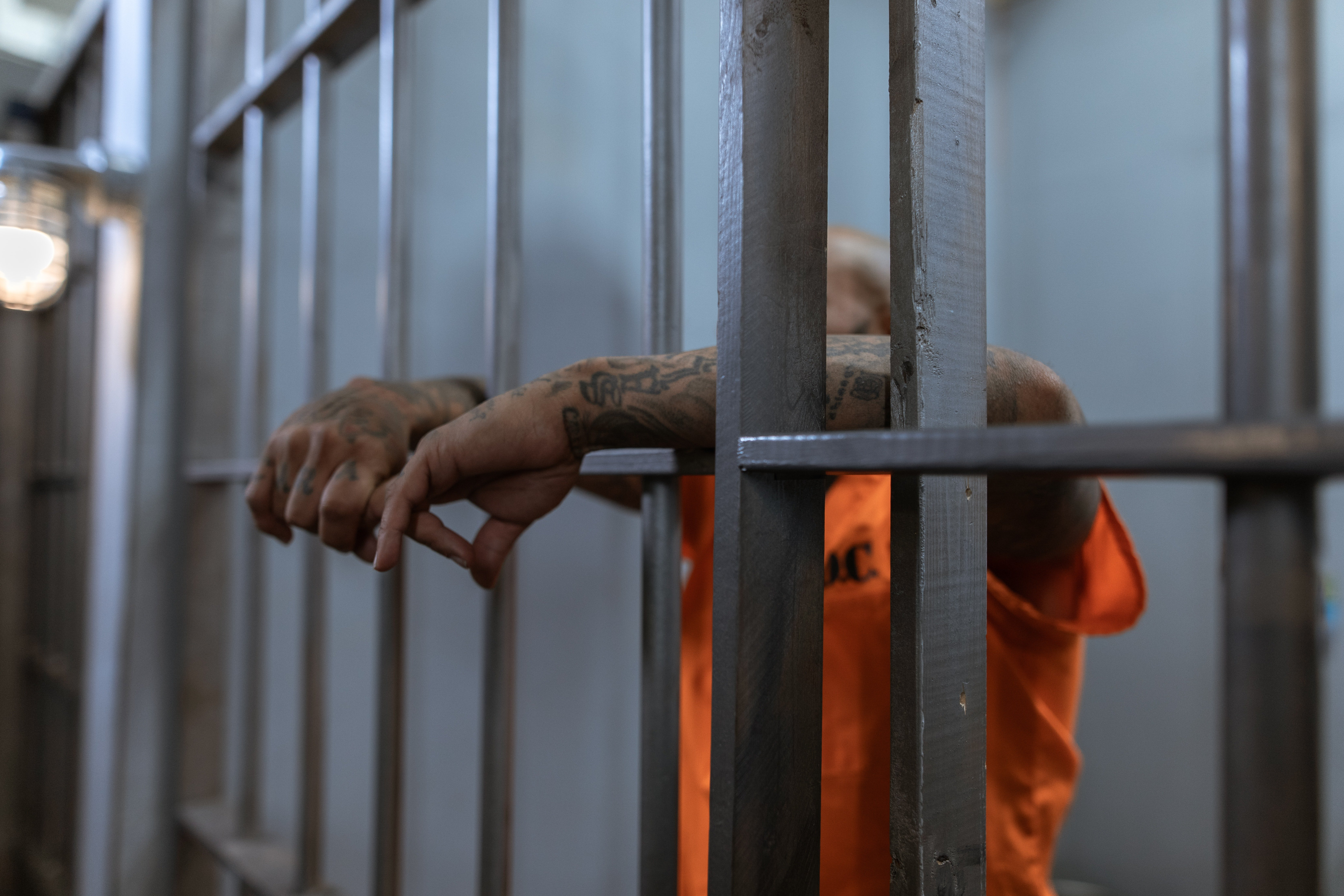Pictured - A male individual behind bars   Source: Pexels