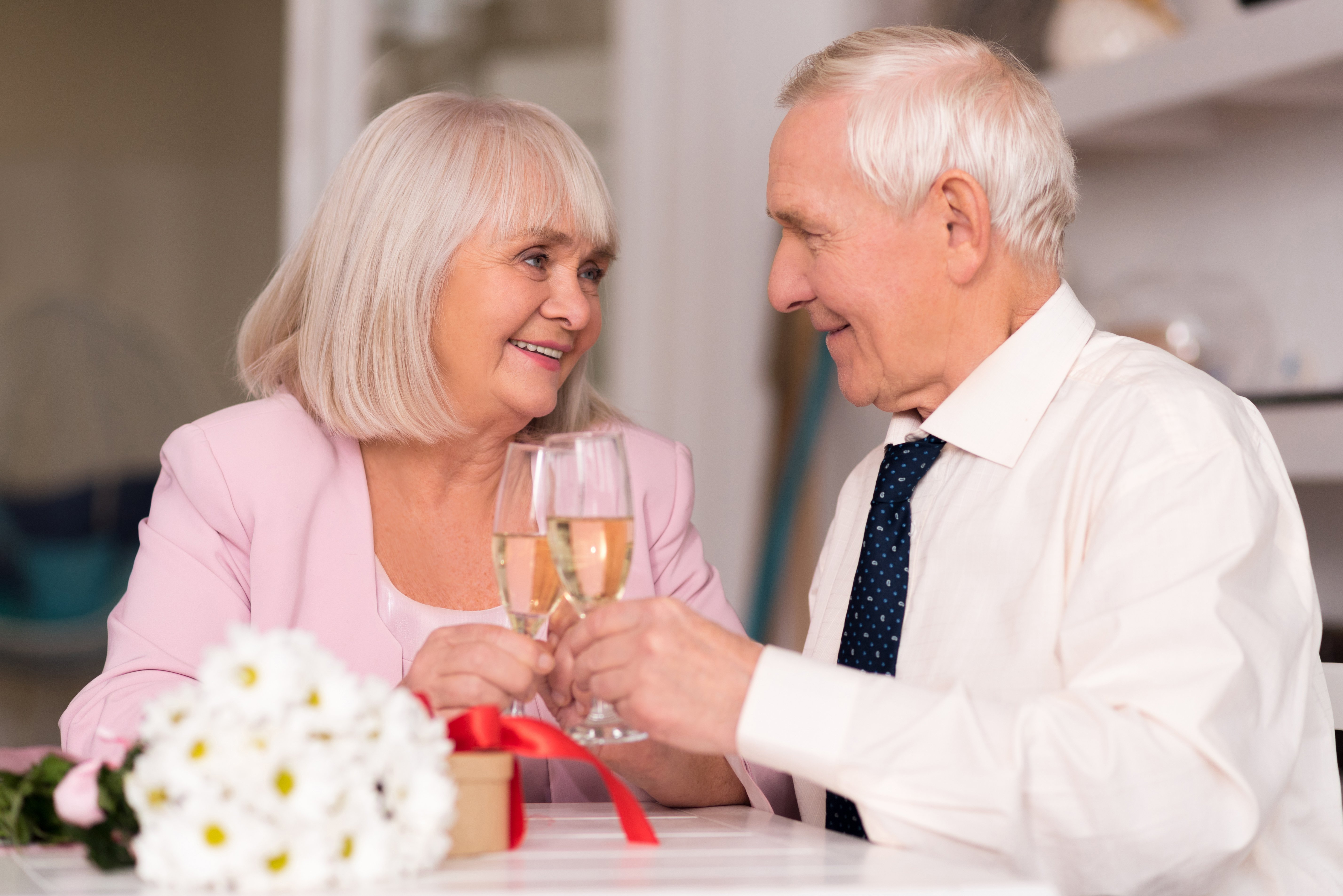 Cheerful senior couple raising their glasses to love | Photo: Shutterstock.com