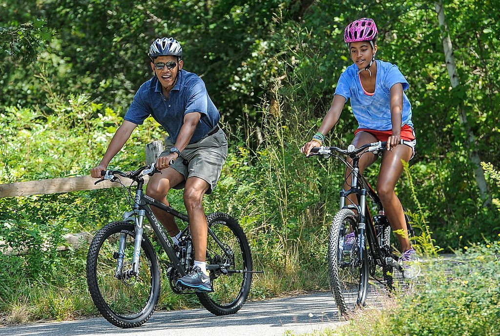 President Barack Obama (L) his daughter Malia Obama ride a bike during a vacation on Martha's Vineyard August 16, 2013. | Photo: GettyImages