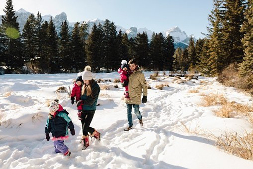 Family hiking below sunny, snowy mountains | Photo: Getty Images