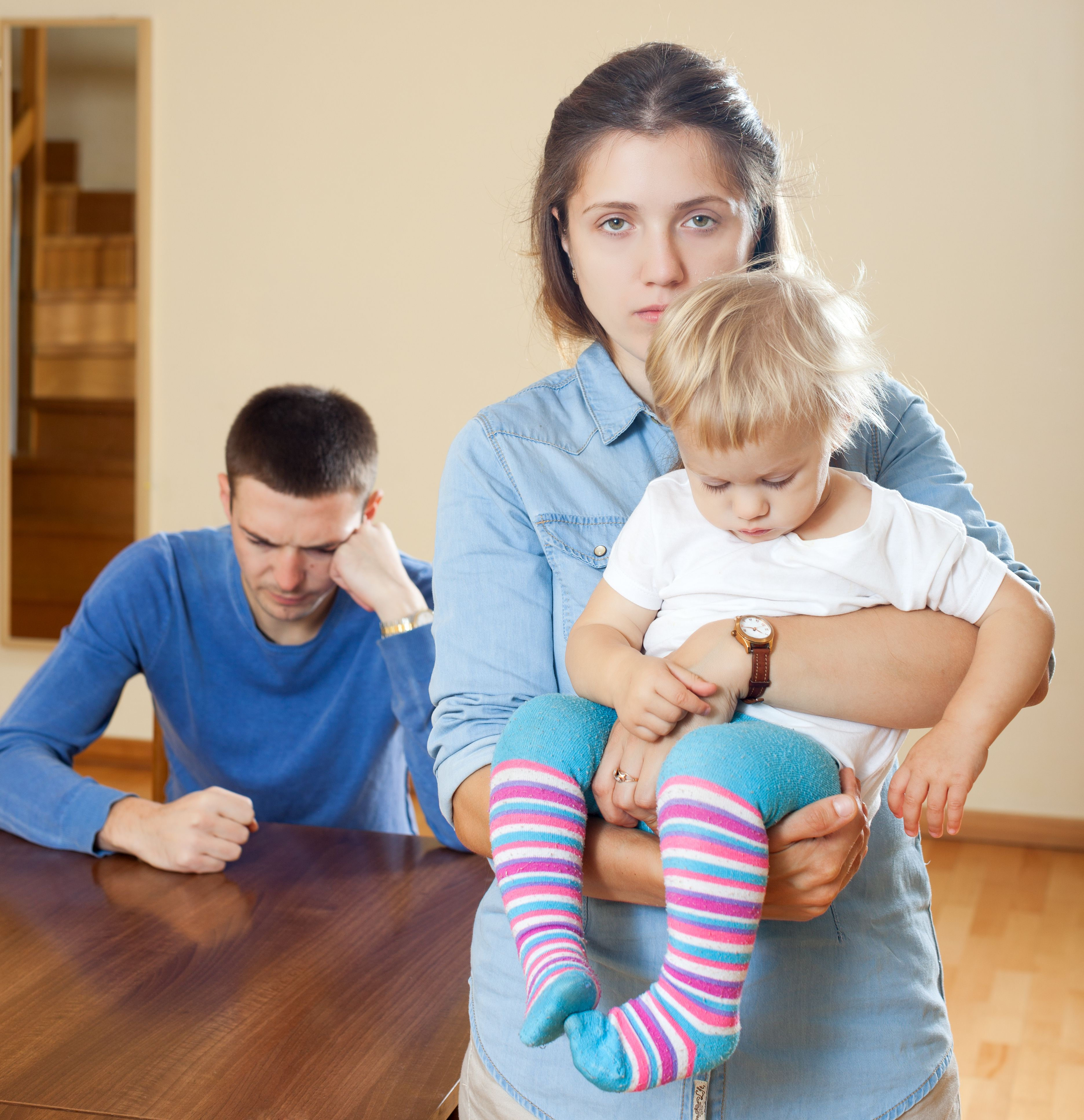 A woman carrying her baby while a man sits behind.   Source: Shutterstock