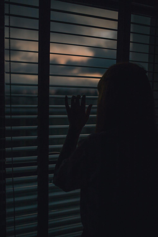 Mujer observando por la ventana. | Imagen: Pexels