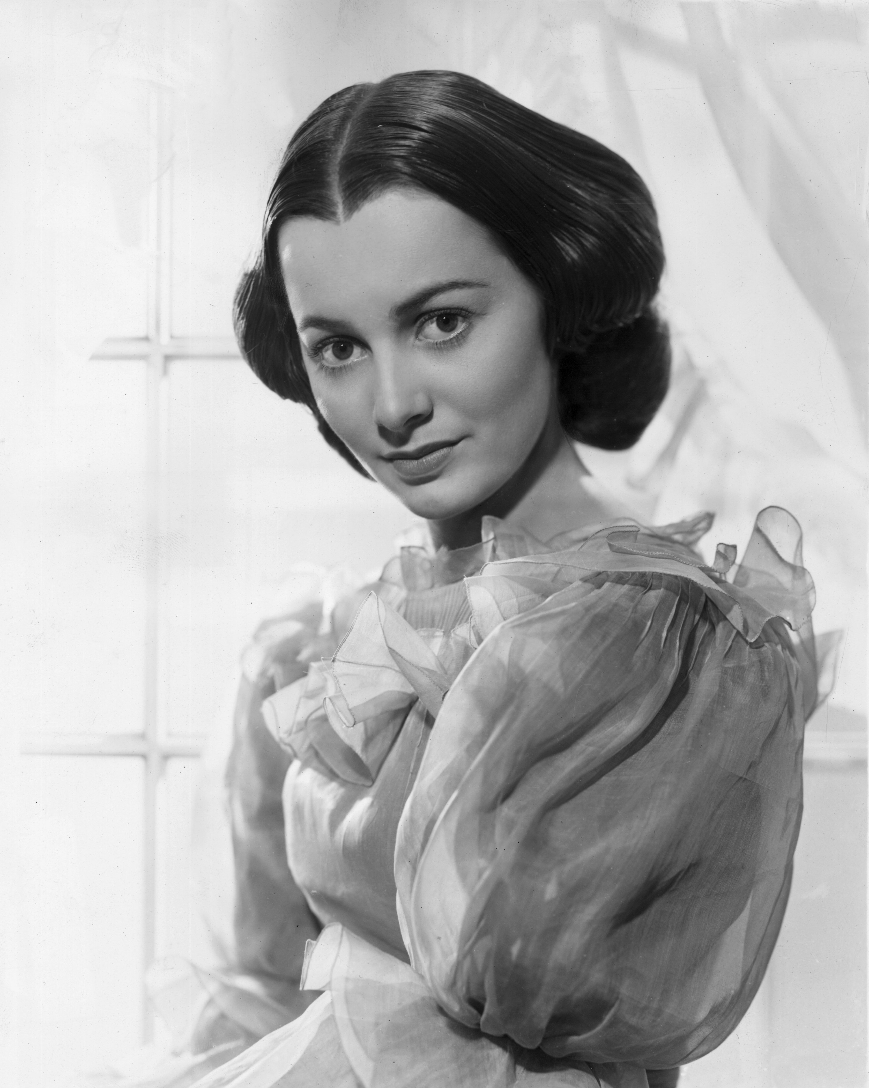 circa 1939: Promotional studio portrait of American actor Olivia de Havilland, standing in front of a window in a promotional portrait for 'Gone With The Wind'. She wears a gown, with her hair parted and pulled back. | Source: Getty Images