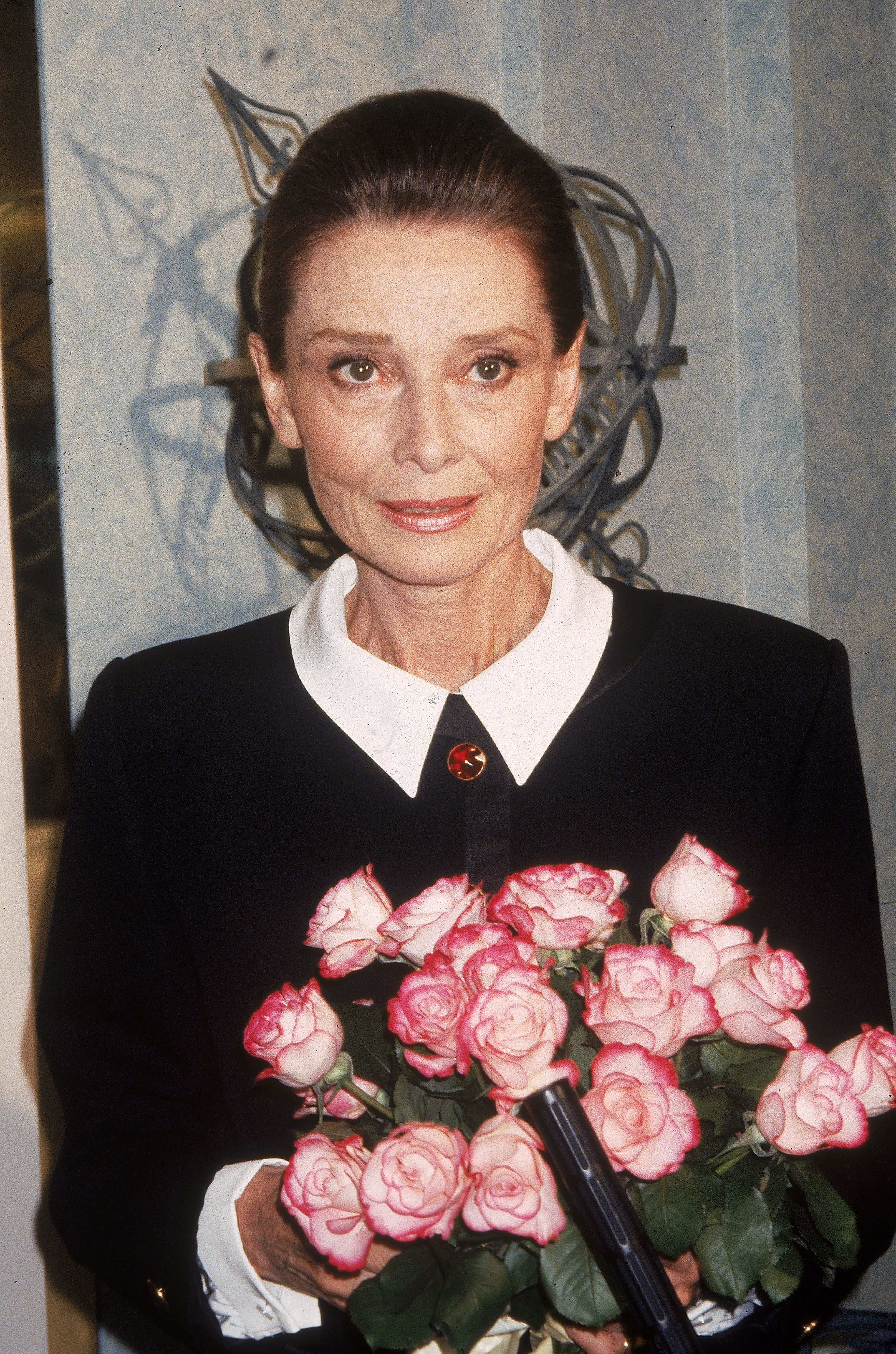 Audrey Hepburn poses with a bouquet of flowers, circa 1985. | Getty Images