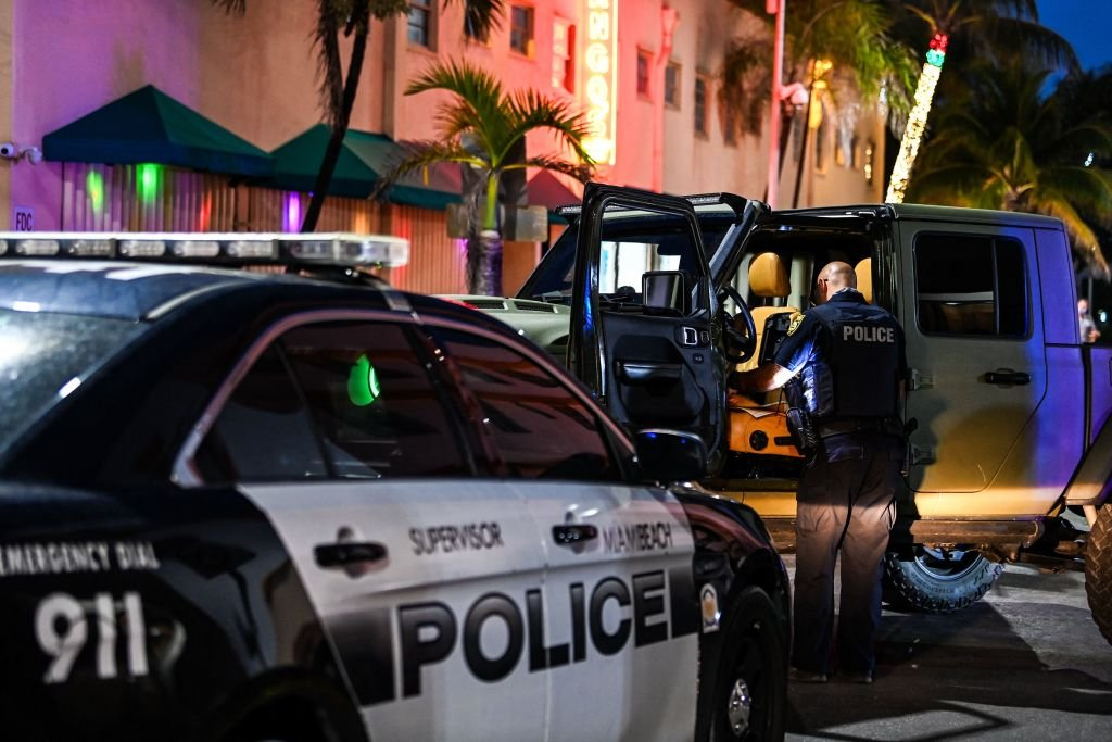 A police officer inspects the inside of a car on Ocean Drive in Miami Beach, on March 22, 2021   Photo: Getty Images